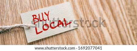 BUY LOCAL label banner natural wooden background. Support small businesses of your community during economic recession by shopping locally in retail stores.