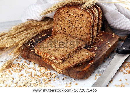 Sliced rye bread on cutting board. Whole grain rye bread with seeds on rustic background #1692091465