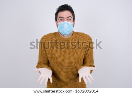 Puzzled and clueless young man with arms out, shrugging his shoulders, saying: who cares, so what, I don't know. Protection against infectious diseases. #1692092014