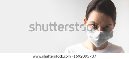 Coronavirus concept. Girl wearing a protective medical mask. Protect your health. Stop the virus and pandemic covid-19. Light gray background. Banner format #1692095737