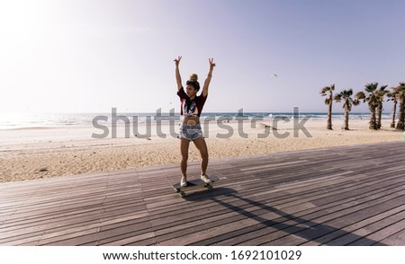 Beautiful woman in her early twenties having some fun with her skaterboard on the promenade by the  beach on a sunny day. #1692101029