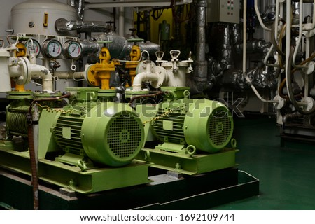 Engine room interior of a big ocean going ship with electrical motors, piping, gauges, valves etc. Royalty-Free Stock Photo #1692109744