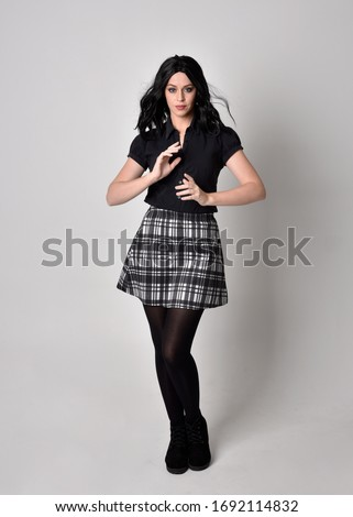 Portrait of a goth girl with dark hair wearing black and plaid skirt with boots. Full length standing pose on a studio background.