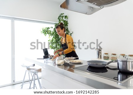 Brunette woman cooking a recipe from a digital tablet in a modern kitchen #1692142285