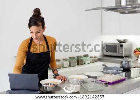 Young brunette woman looking at her digital tablet for a recipe on the web and cooking in a modern kitchen #1692142357