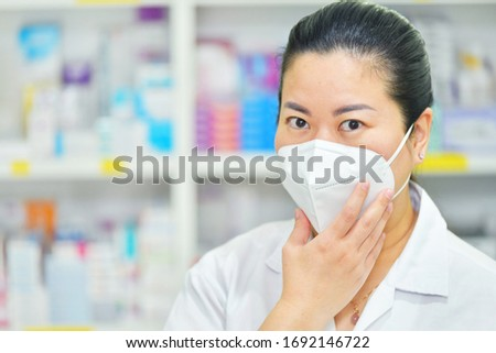 Pharmacist wear N95 mask on many medicine shelf background. Coronavirus (COVID-19)concept of disease, flu treatment and protection.copy space #1692146722