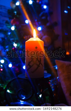 A large candle burns against the background of a garland with shining lights. Vertical photo, defocus. Mystic esoteric romance divination mood christening Christmas carol setcers #1692148276