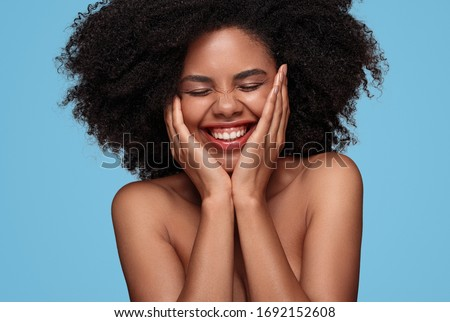 Positive young black female with bare shoulders and beautiful skin touching face and laughing with eyes closed on blue background #1692152608