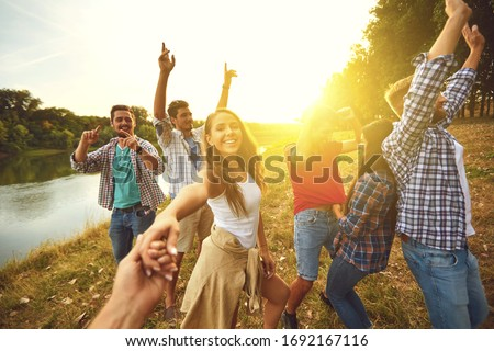 A group of friends dancing cheerfully at a picnic party in nature. #1692167116