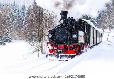 Steam train rushes through the snow-covered forest. Winter steam train view. Steam train ride in winter snow forest #1692174580