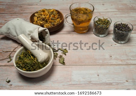 Phytotherapy. Composition of dry herbs for herbal medicine.  Herbal decoction of calendula and various dried herbs in linen bags and cups on a light wooden background. Free space. #1692186673