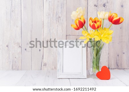 Tulip flower in glass vase with picture frame decor on wooden table background wall at home, close up, Mother's Day design concept.