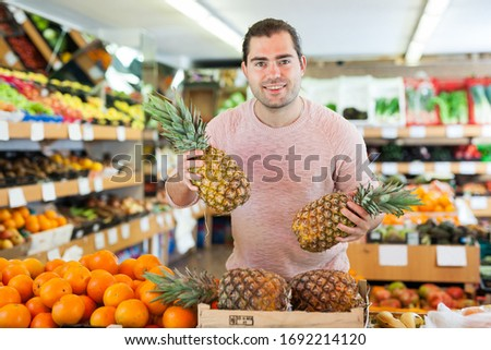 Smiling man customer holding  fresh pineapples in hands  on the supermarket #1692214120