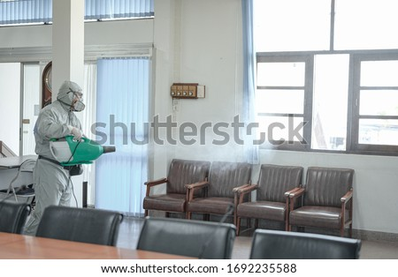 Disinfecting of office to prevent COVID-19, person in white hazmat suit with disinfect in office, coronavirus concept #1692235588