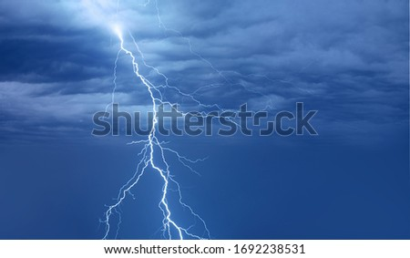 Lightning strikes between blue stormy clouds.