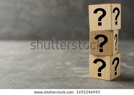 Wooden cubes with question marks on grey stone table. Space for text #1692246943