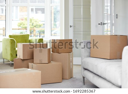Cardboard carton boxes stack with household belongings in modern house living room. Packed containers on floor in new home. Royalty-Free Stock Photo #1692285367