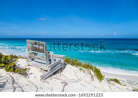 Relaxing bench with stunning caribbean ocean and beach of bahamas in the background