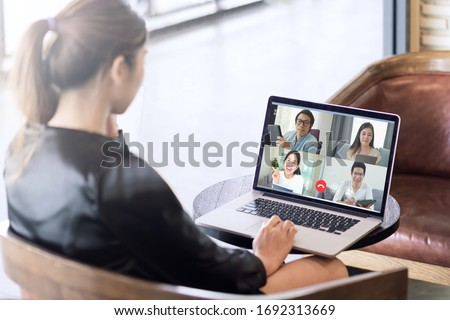 Back view of business woman talking about sale report in video conference. Asian team using laptop and tablet online meeting in video call.Working from home, Working remotely and Self isolation. #1692313669