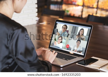 Back view of business woman talking about sale report in video conference. Asian team using laptop and tablet online meeting in video call.Working from home, Working remotely and Social isolation. Royalty-Free Stock Photo #1692335203