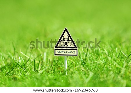 yellow icon, warning sign for biological hazards and the message SARS-CoV-2 on Bright spring grass field with sunlight bokeh background. symbol for coronavirus infection. warning sign COVID-19 #1692346768