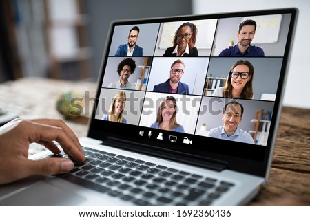 Man Working From Home Having Online Group Videoconference On Laptop Royalty-Free Stock Photo #1692360436