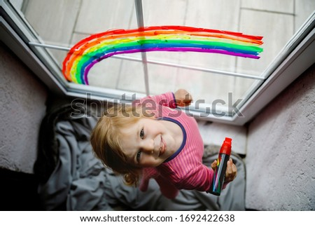 Adoralbe little toddler girl with rainbow painted with colorful window color during pandemic coronavirus quarantine. Child painting rainbows and hearts around the world with words Let's all be well.