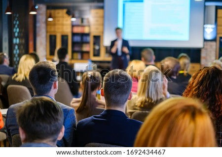 Audience listens lecturer at workshop in conference hall Royalty-Free Stock Photo #1692434467