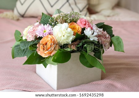 bouquet of orange and white flowers in a box stands on a pink background #1692435298