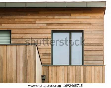 Modern wooden facade with flat roof and aluminium window Royalty-Free Stock Photo #1692465715