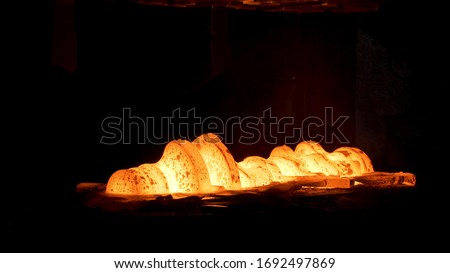 Steel quenching at high temperature in industrial furnace at the workshop of a forge plant. Scene. Process of cooling, heat treatmen, blacksmith and metallurgical industry, steelmaking. #1692497869