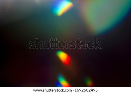 Lens flare and light leak haze texture on a black background.