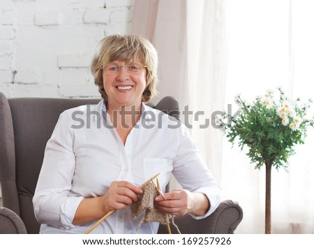 Portrait of a smiling middle age woman knitting on spokes at home #169257926