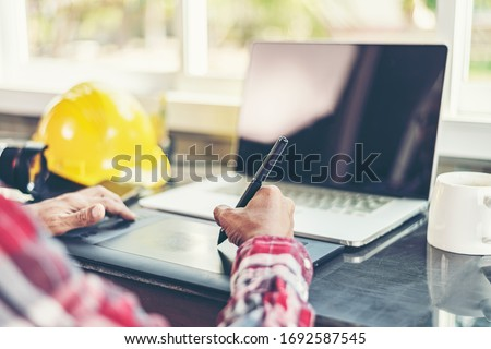 Work from home.Professional graphic editor retouching images with stylus pen in hand.Retoucher processing photos on laptop computer using tablet.Creative freelancer retouched image on notebook