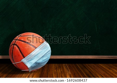 Basketball wearing surgical mask on a background chalk board with copy space for text. Concept of COVID-19 coronavirus pandemic affecting basketball seasons due to game or league suspensions.