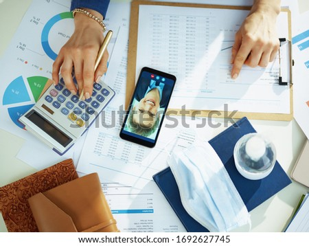 Upper view of 40 years old business woman having video chat while working with documents at the table. #1692627745
