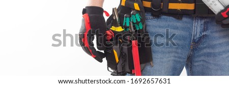 Electrician or professional Builder in an installer's belt with tools on a white background. Electrician's tools in black bags on the worker's belt. Banner with space for text Royalty-Free Stock Photo #1692657631