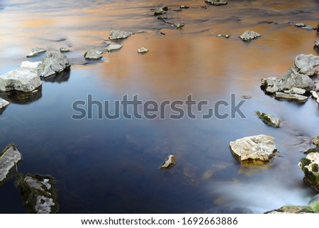 Calm atmospheric picture of large stones lying in a river in the evening, around which the water flows very calmly and which form a frame