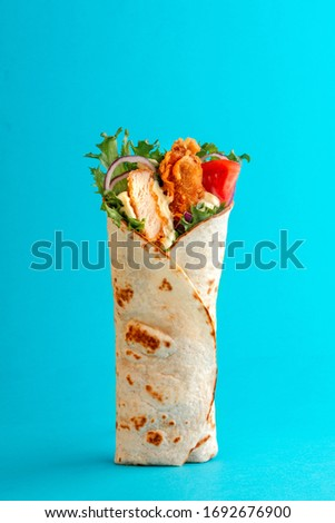 Fresh chicken roll with fresh tomatos, salad, cheese and onions isolated on bright blue background. Side view. Royalty-Free Stock Photo #1692676900