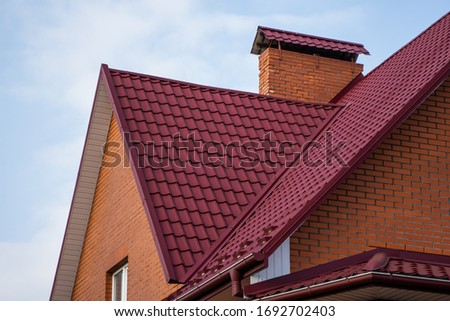 Red metal tile roof. Roof metal sheets. Modern types of roofing materials. Roof of the house, metal roof tile against the blue sky. Building. #1692702403