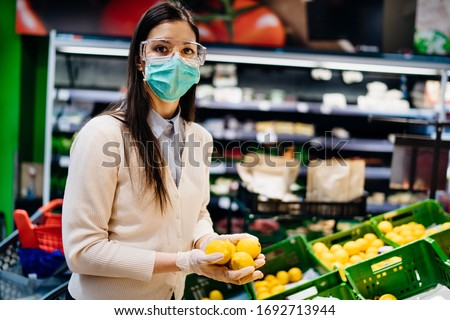 Woman with protectivmask buying in grocery supermarket for fresh produce,budget shopping for citrus fruit during the pandemic.Natural source of vitamins and minerals.Coronavirus COVID-19 immunity #1692713944