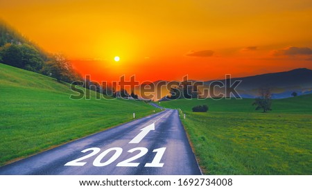 Empty open asphalt road and New year 2021 concept. Driving on empty road goals against sun in mountains to upcoming 2021 and leaving behind old years. Concept for growth success, passing time future. Royalty-Free Stock Photo #1692734008