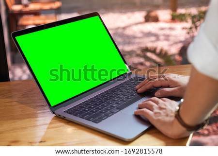 Mockup image of a woman using and typing on laptop computer with blank green desktop screen on wooden table