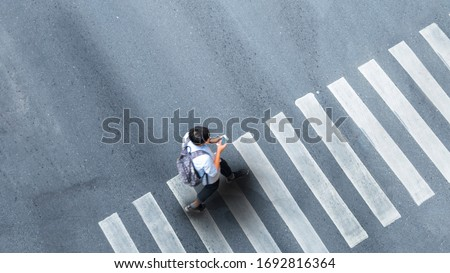 Human life in Social distance. Aerial top view with blur man with smartphone walking at pedestrian crosswalk on grey pavement street road with empty space. #1692816364