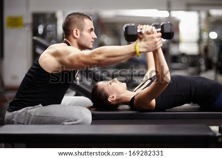 Personal trainer helping woman working with heavy dumbbells Royalty-Free Stock Photo #169282331