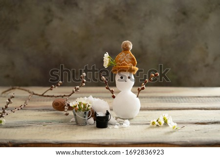 the spring equinox  or hello spring concept. Funny card with broken snowman and melted snow in buckets. Flowers and snow on the scales. Copy space for text. Horizontal banner