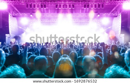 Music festival crowd,concert spectators in front of a bright stage with live music Royalty-Free Stock Photo #1692876532