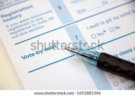 Closeup of 'Vote-by-mail' section on a voter registration form, with ballpoint pen laying on the form. #1692885346