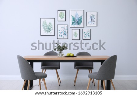 Stylish room interior with modern table, chairs and paintings of tropical leaves. Idea for design Royalty-Free Stock Photo #1692913105