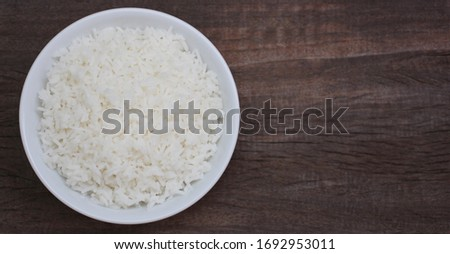 Jasmine cooked rice in white bowl on wooden background using as healthy food, thai food concept. top view #1692953011